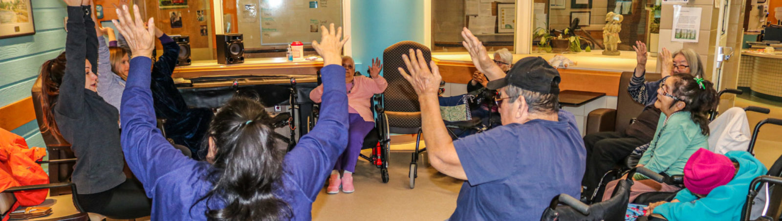 Group image of Elders at our Extended Care Unit doing chair-yoga.