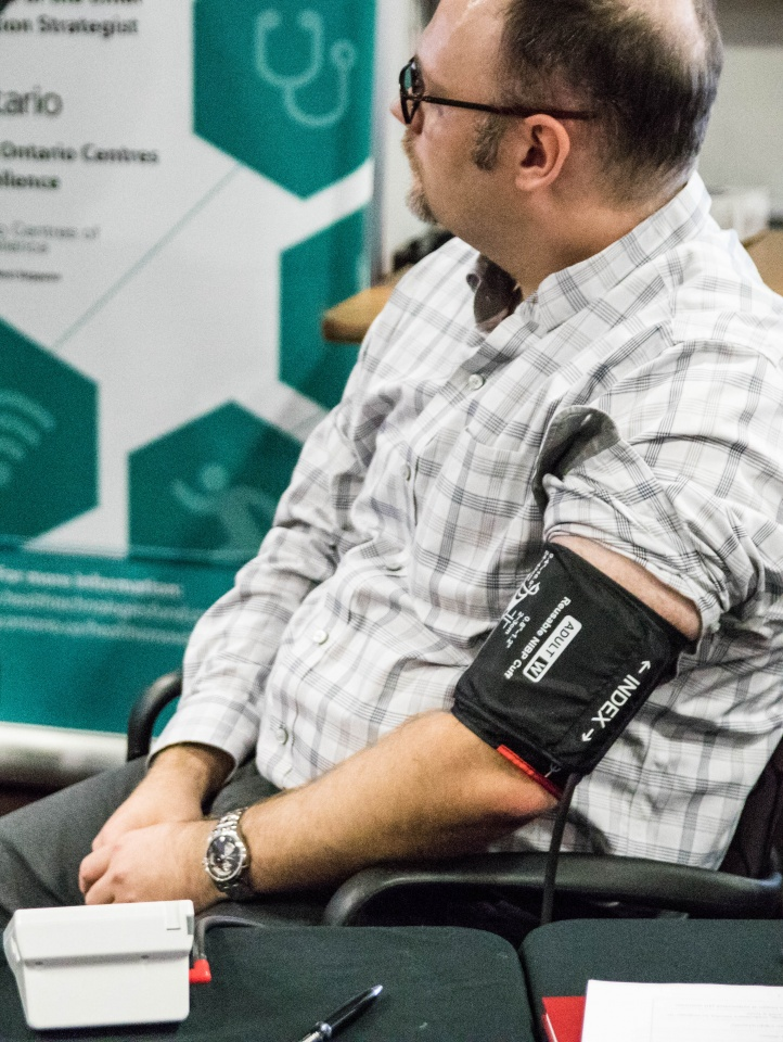 Man sitting in chair getting blood pressure checked.